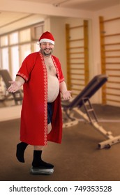 Cheerful Santa weighing himself on one leg on blurred gym background. Man is ready to burn fat in the gym which gained during Christmas holidays