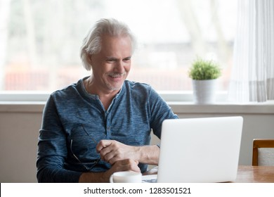 Cheerful satisfied retired mature person sitting at table in the kitchen working on computer received good positive news from bank using laptop for entertaining watching online program or funny video