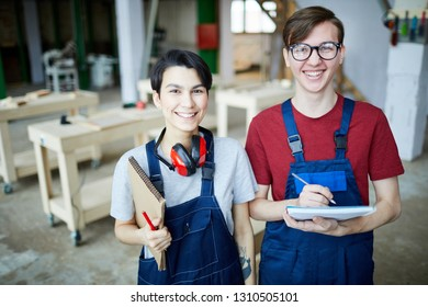 Cheerful satisfied young students in workwear standing in modern carpentry classroom and laughing while looking at camera and writing down information in sketchpad