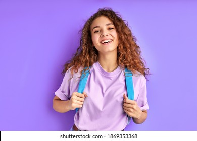 fröhliches Schulmädchen mit Tasche, die sich auf der Kamera posiert, einzeln auf violettem Hintergrund, fröhliches Weibchen mit lockigem Haar Lächeln, gerne zur Schule gehen. Bildungskonzept
