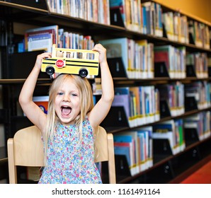 Cheerful schoolgirl holding toy school bus above her head in the library