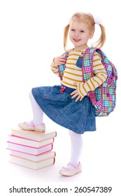 cheerful schoolgirl with satchel behind him holding his leg on a pile of books - isolated on white.