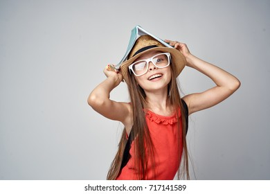 cheerful schoolgirl smiling in a hat and glasses on her head holding a notebook with a house on a gray background, knowledge, educatio