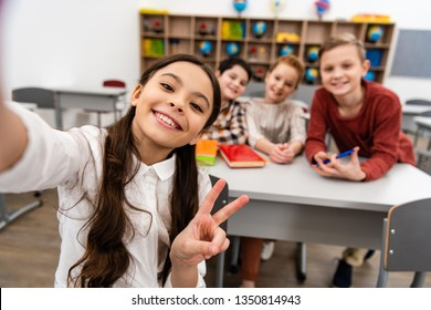 Cheerful schoolgirl taking selfie with friends and showing peace sign in classroom