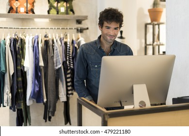 Cheerful seller man in clothing store. Working on computer