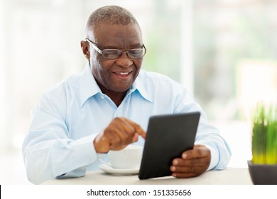 cheerful senior african american man using tablet computer at home