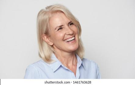 Cheerful senior businesswoman isolated on grey studio wall