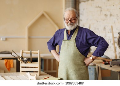cheerful senior citizen is ready to work in the workshop. hardworking grandpa in the home workshop