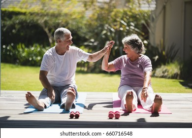 Cheerful senior couple giving high five while exercising together on mat at porch