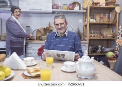 Cheerful senior couple having breakfast  and reading a news at home