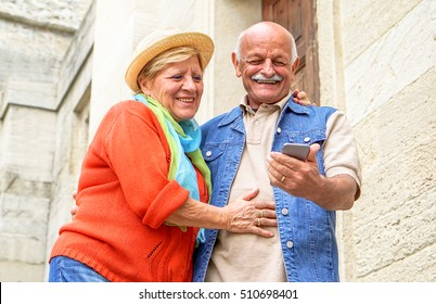 Cheerful senior couple having fun with new smart phone social trends - Happy old people using mobile device outdoor - Concept of technology elderly active - Warm filter with soft vivid editing