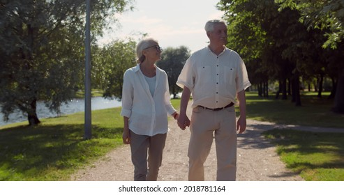 Cheerful senior couple holding hands walking outdoors in city park having romantic date. Portrait of happy aged man and woman in love stroll in summer park near lake
