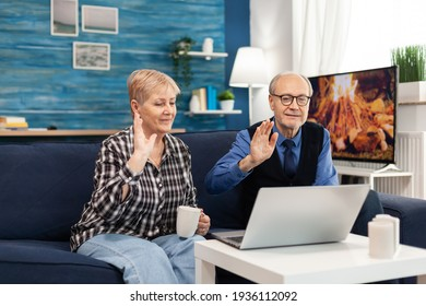 Cheerful senior couple in living room waving at webcam during online call. Happy elderly man and woman saying hello to laptop webcam sitting on sofa in the course of video conference.