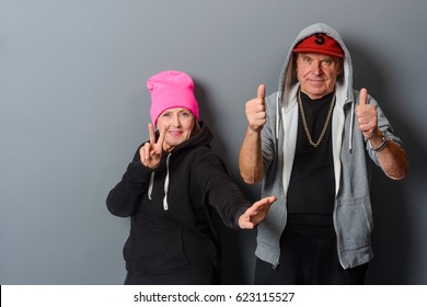Cheerful senior couple show with gestures peace and thumb up signs. Grandparents trying to be young. Horizontal photo with a gray wall in the background.