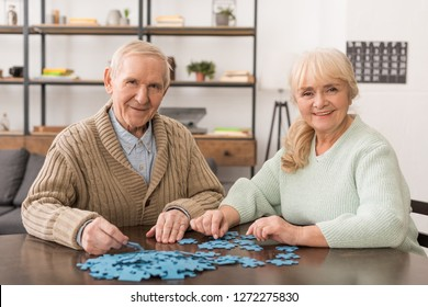 cheerful senior couple smiling and playing puzzles at home