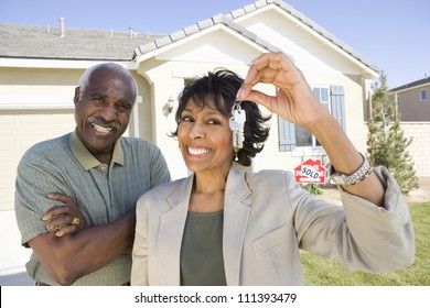 Cheerful senior couple standing in front of house for sale with key