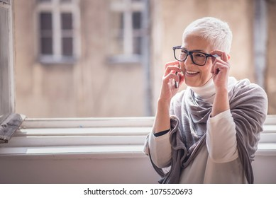 Cheerful senior elderly lady having a phone talk next to a big window in her house