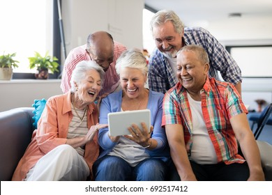 Cheerful senior friends looking at digital tablet while resting in nursing home