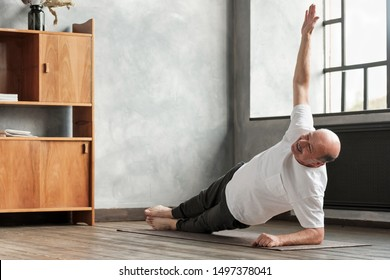 Cheerful senior hispanic man doing a side plank exercise at living room. Doing yoga at home at old age.
