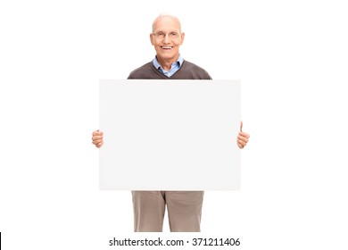 Cheerful senior holding a blank white signboard and looking at the camera isolated on white background