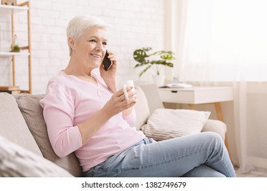 Cheerful senior lady having phone call on her smartphone and gossiping, enjoying fresh tea, free space
