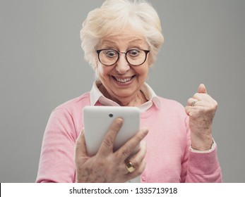 Cheerful senior lady using a digital tablet and receiving an amazing surprise, she is a winner and celebrating with fist raised