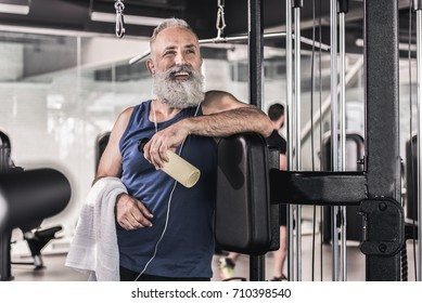 Cheerful senior male is smiling while resting in sport center