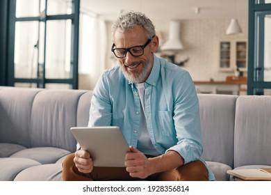 Homme âgé joyeux vêtu d'un vêtement décontracté avec tablette numérique tout en s'asseyant sur le canapé à la maison