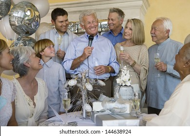 Cheerful senior man celebrating start of retirement with family and friends
