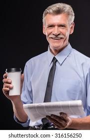 Cheerful senior man with coffee and newspaper on dark background.