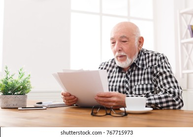 Cheerful senior man looking photos, sitting at table, copy space. Good memories concept