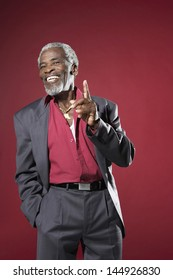 Cheerful senior man in suit making hand gesture against red background