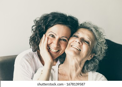 Cheerful senior mother and adult daughter posing at home. Happy elderly lady touching cheek of middle aged woman, laughing and smiling at camera. Affection concept