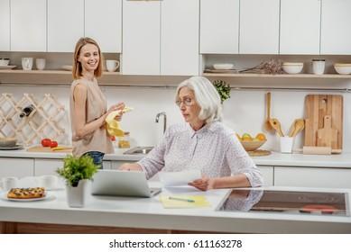 Cheerful senior mother using modern technology