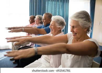 Cheerful senior people exercising with arms raised at retirement home