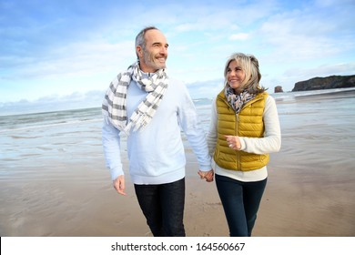 Cheerful senior people walking on the beach