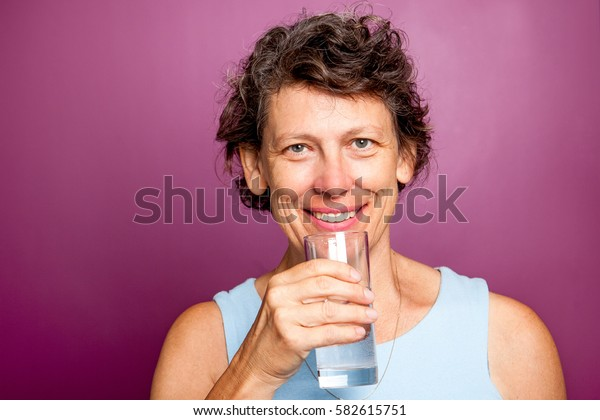 Cheerful senior sportswoman with glass of water