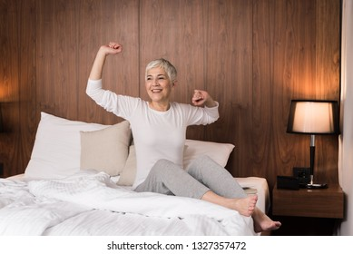 Cheerful senior woman with big beautiful smile waking up and stretching in her bedroom, Joy of the new day concept