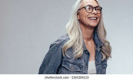 Cheerful senior woman in casuals looking away and smiling over grey background. Happy mature woman in denim shirt and eyeglasses.