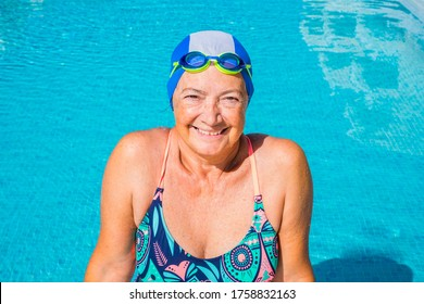 Cheerful senior woman doing sport in the outdoor swimming pool under the sun. Blue swim cap and goggles. Healthy lifestyle of one retired people