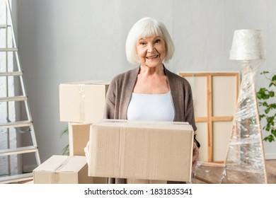 cheerful senior woman holding cardboard box and looking at camera, moving concept