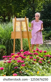 Cheerful senior woman painting in garden on sunny day.