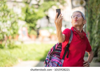 Cheerful senior woman sending kisses to her family or friends over her cell phone, enjoying her summer trip
