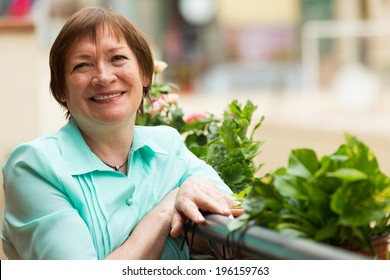 Cheerful senior woman sitting on balcony and smiling