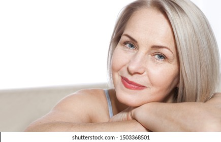 Cheerful senior woman smiling while looking away at spa. Happy mature woman after spa massage anti-aging treatment on face. Selective focus on macro face. Realistic images with their own imperfections