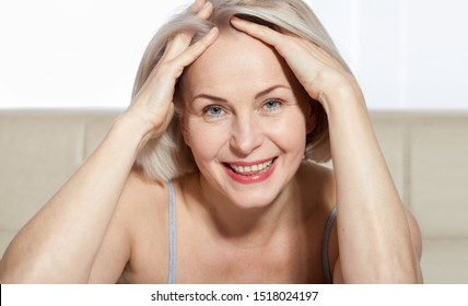 Cheerful senior woman smiling while looking away at spa. Happy mature woman after spa massage and anti-aging treatment on face. Macro face. Selective focus on face. Realistic images.