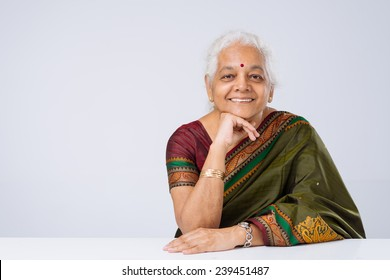 Cheerful senior woman in traditional clothes sitting at the table and looking at the camera