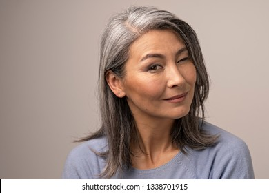Cheerful Senior Woman Winks And Smiles At Camera. Beautiful Asian Woman With Grey Hair Winking With One Eye And Smiling. Portrait.