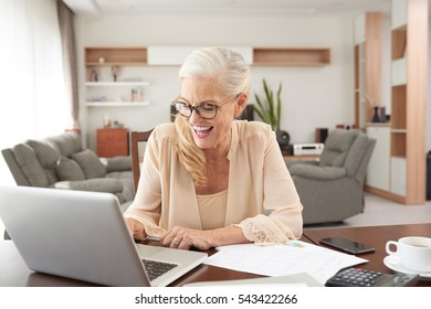 Cheerful senior woman working on laptop at home