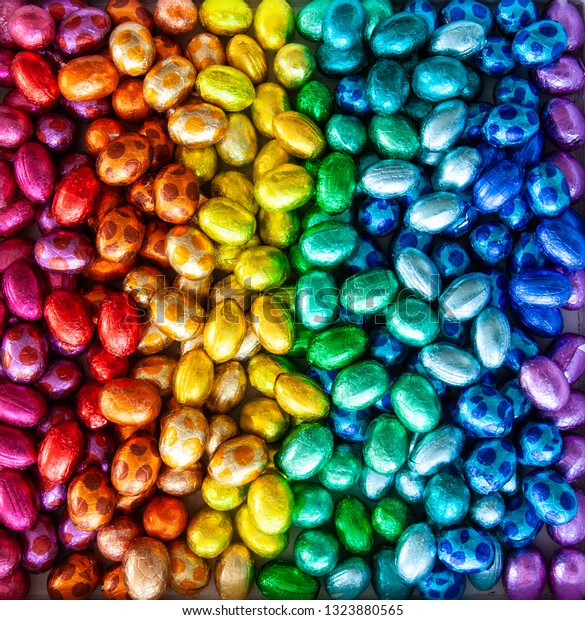 Cheerful shiny chocolate eggs in rainbow colors for a Happy Easter